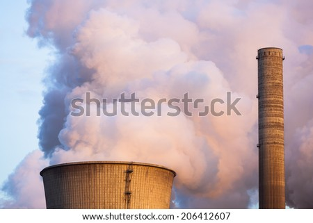A steaming cooling tower in the evening illuminated by warm sunlight