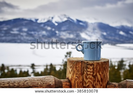 a steaming cup of coffee with beautiful mountains in the background - stock photo