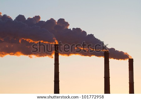 A steaming power plant pipes against sunset sky