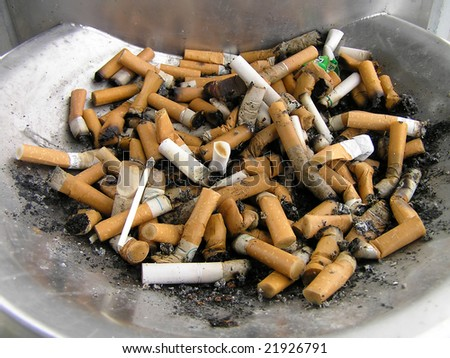 A steel ash tray full of cigarette ends