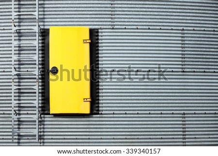 A steel bin adorned with a bright yellow door and ladder.