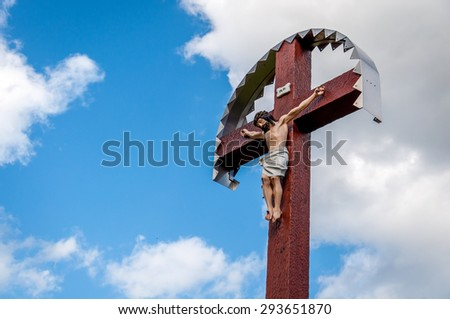 A steel cross with crucifix against a blue sky with clouds.  - stock photo