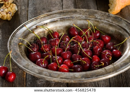 A steel plate full of cherries in the focus of the camera. Juicy seductive berries for a sweet tooth. Delicious snack. - stock photo