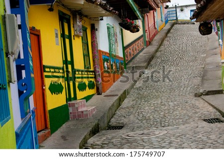 A steep street in Guatape (Colombia). Every building/house has tiles along the facade's lower walls in bright colors and dimensioned images.