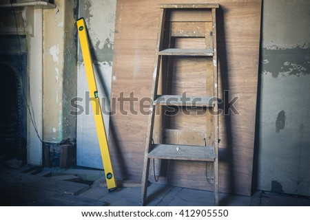 A step ladder and a spirit level against a wall with a sheet of plywood - stock photo