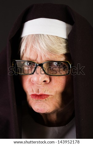 A stern looking nun with a judging expression - stock photo