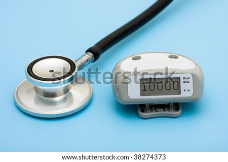 A stethoscope and a pedometer on a blue background, walking for a healthy heart