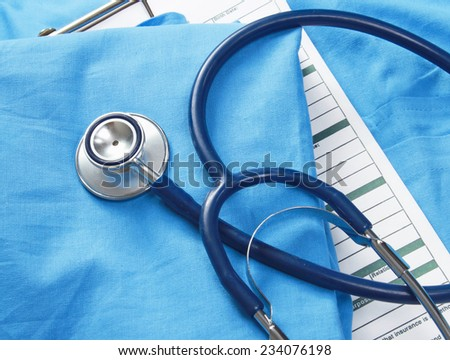 A stethoscope and RX prescription are lying on a medical uniform. - stock photo