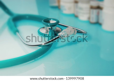 A stethoscope in front of medicine bottles - stock photo