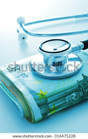 a stethoscope on a wad of euro bills, depicting the concept of the health care industry or the health care costs - stock photo
