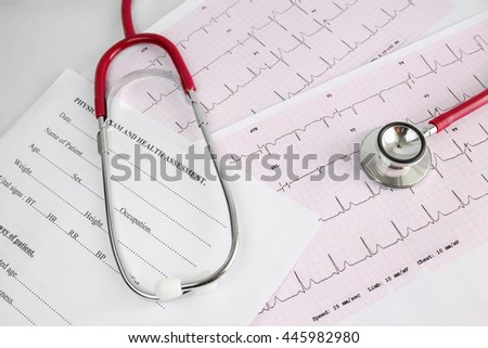 A Stethoscope on the waveform from an ECG graph and health assessment form as a background. - stock photo