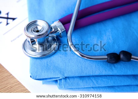 A stethoscope shaping a heart and a clipboard on a medical uniform, closeup