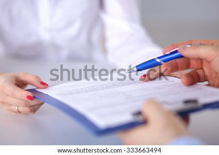 A stethoscope shaping a heart and a clipboard on a medical uniform, closeup - stock photo