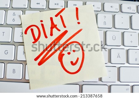 a sticky note is on the keyboard of a computer reminder: diet - stock photo
