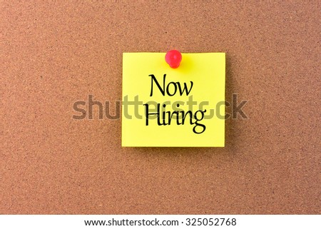 A sticky note on a wood with the words now hiring on it - stock photo