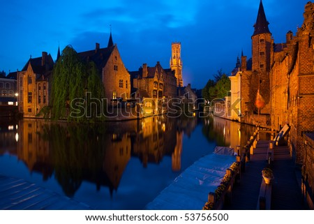 A still canal reflecting the old red brick buildings and belfry of the historic old town on Rozenhoedkaai Street at dusk blue hour in Bruges, Belgium. Horizontal copy space - stock photo