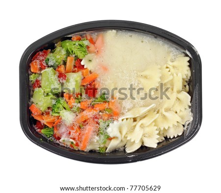 A still frozen TV dinner with pasta and vegetables in black dish. - stock photo