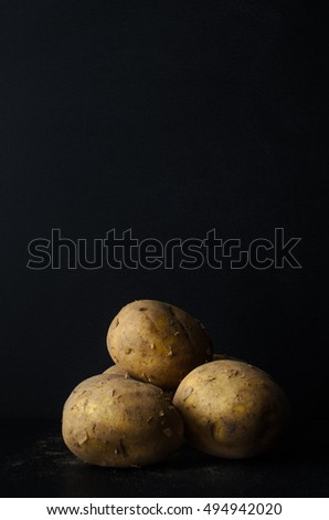 A still life group of fresh, whole, unpeeled potatoes with scattering of soil on black slate with black chalkboard background providing copy space above.