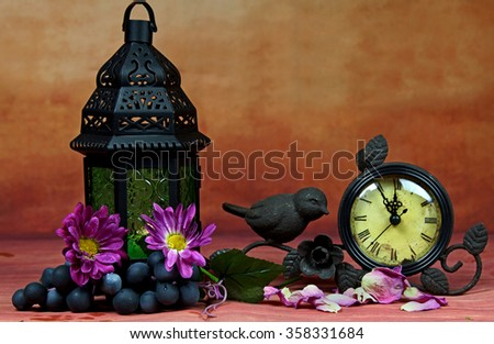 A still life of a lantern and a clock with spring flowers, selective focus. - stock photo