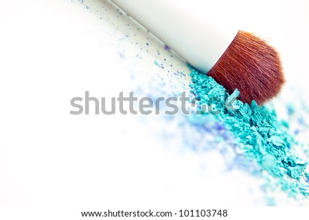 a still-life of colourful eyeshadow powder and make-up brush - stock photo