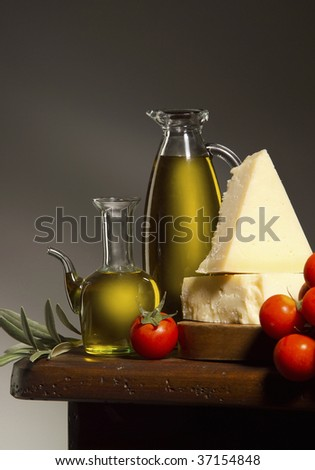 A still life of olive oil, parmesan and tomato on a wooden table - stock photo
