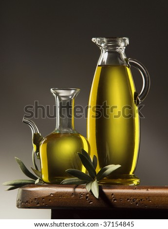 A still life of two bottles of olive oil wiyh leaves on a wooden table - stock photo