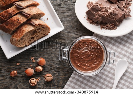 A still life with a hazelnut spread glass jar, milk chocolate, hazelnuts and fresh rye French bread pieces. Top view. - stock photo