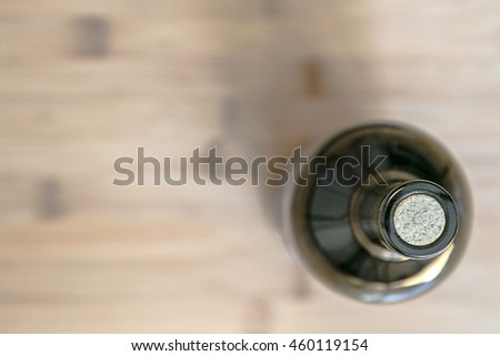 A still life with a wine bottle standing on a wooden surface blurred background, view from above
