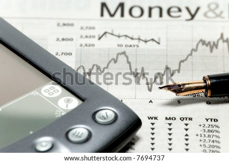 a stock market chart with a pen and pda - stock photo