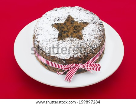A stock photo of a Christmas Fruit cake on a red background - stock photo