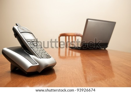 A stock photo of a cordless phone and laptop sit on an empty table. - stock photo