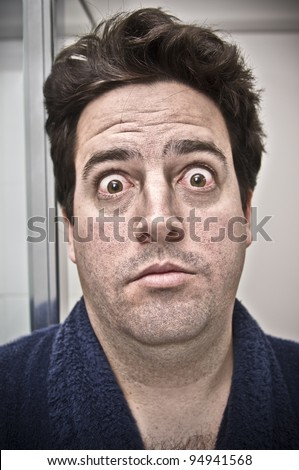 A stock photo of a man surprised by his own face the morning after a big night