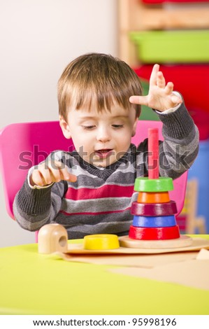 A stock photo of a young boy playing with stacking blocks in a nursery room - stock photo