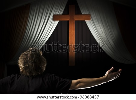 A stock photo of a young man praying with open arms before a cross. - stock photo