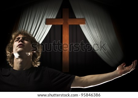 A stock photo of a young man praying with open arms in from of a cross. - stock photo