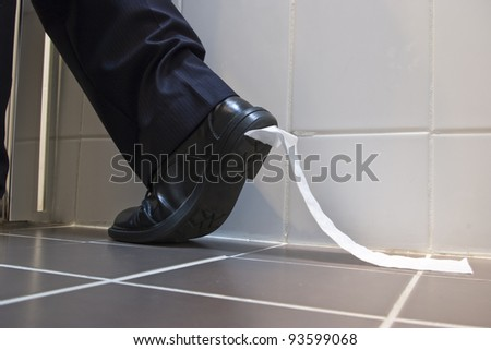 A stock photo of toilet paper stuck to the sole of a dress shoe - stock photo
