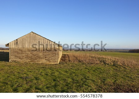 a stone and wooden farm building with a view of the vale of york in a yorkshire wolds landscape under a clear blue sky in winter