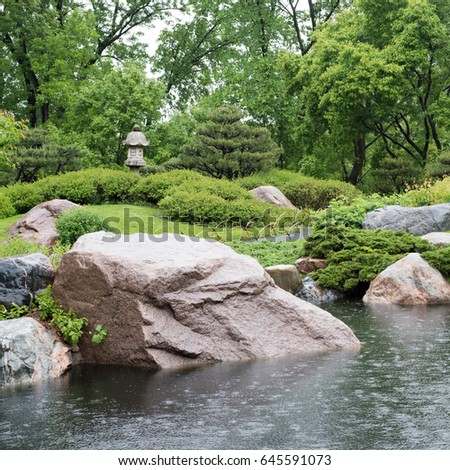 a stone bridge crosses a pond in a japanese garden - Japanese Garden Stone Bridge