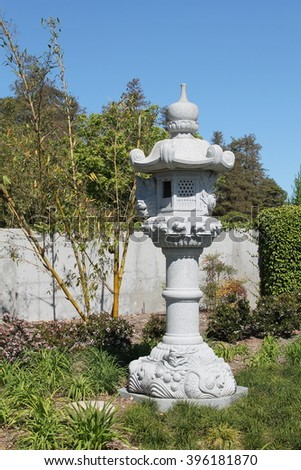 A stone carved Japanese lantern sits in a Zen meditation garden.