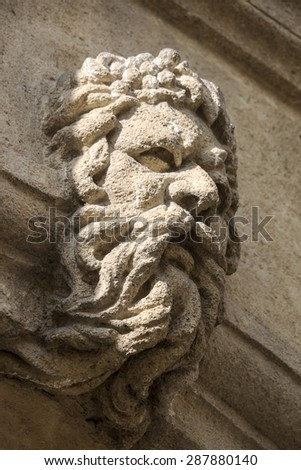 A stone carving of a man with flowing beard that has been applied to the facade of a building in Aix en Provence in Southern France. - stock photo
