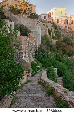 A stone path along the slope with bushes and houses on top at sunset - stock photo