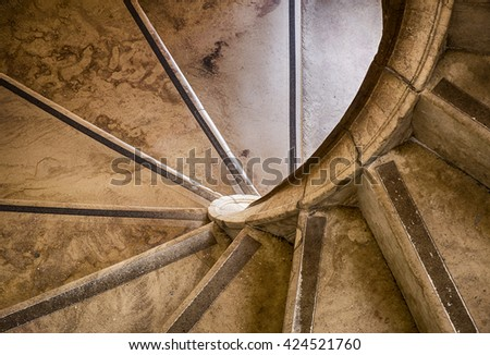 A stone staircase winds its way upwards with a spiral geometric shape in an old building in Sintra, Portugal.