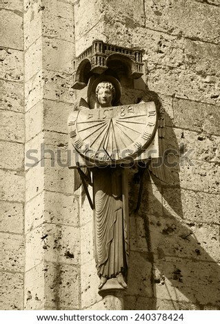 A stone statue of Angel holding sundial with the date 1528. Architectural detail of  the cathedral in Chartres (France). Aged photo. Sepia. - stock photo
