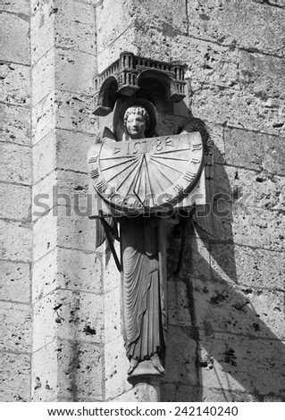 A stone statue of Angel holding sundial with the date 1528. Architectural detail of  the cathedral in Chartres (France). Aged photo. Black and white. - stock photo