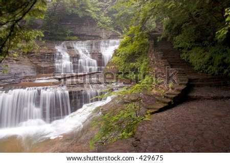 A stone walkway leads you along this gorge trail past many beautiful waterfalls like this one. - stock photo