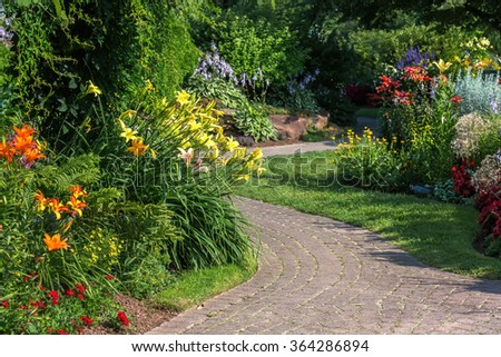 A stone walkway winding through a tranquil garden. - stock photo