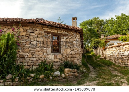 A stone wall and an old house from Arbanasi, Bulgaria. - stock photo