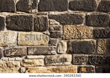 A stone wall in Edinburgh Castle shows a pattern from unevenly sized light and dark stones and mortar. - stock photo