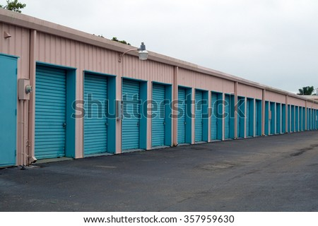 A storage unit building showing long row of doors with diminishing perspective.