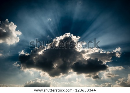 A storm grey cloud blocking the sun, giving the ray of light at the background - stock photo